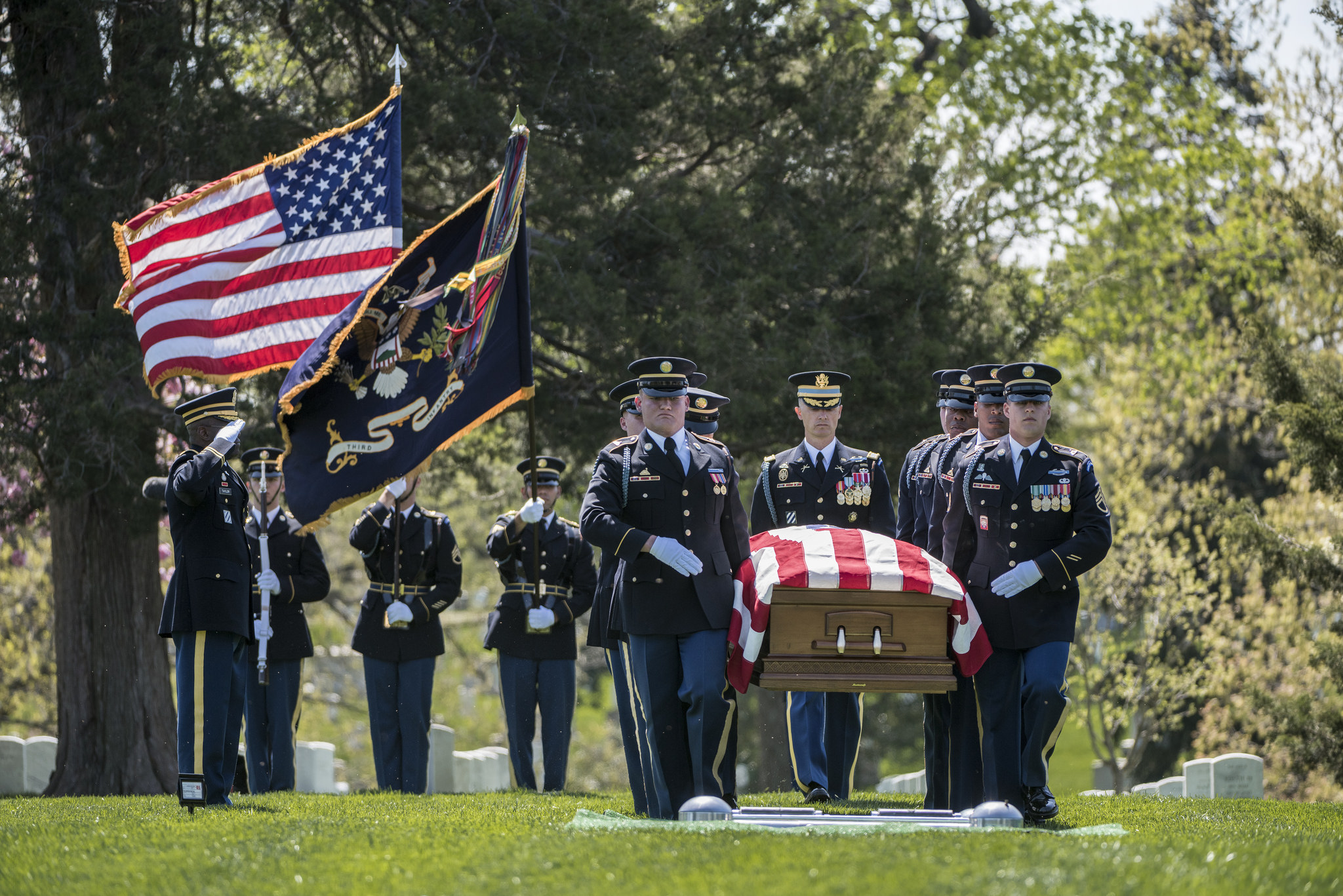 Soldiers in dress uniform carry a flag-draped casket