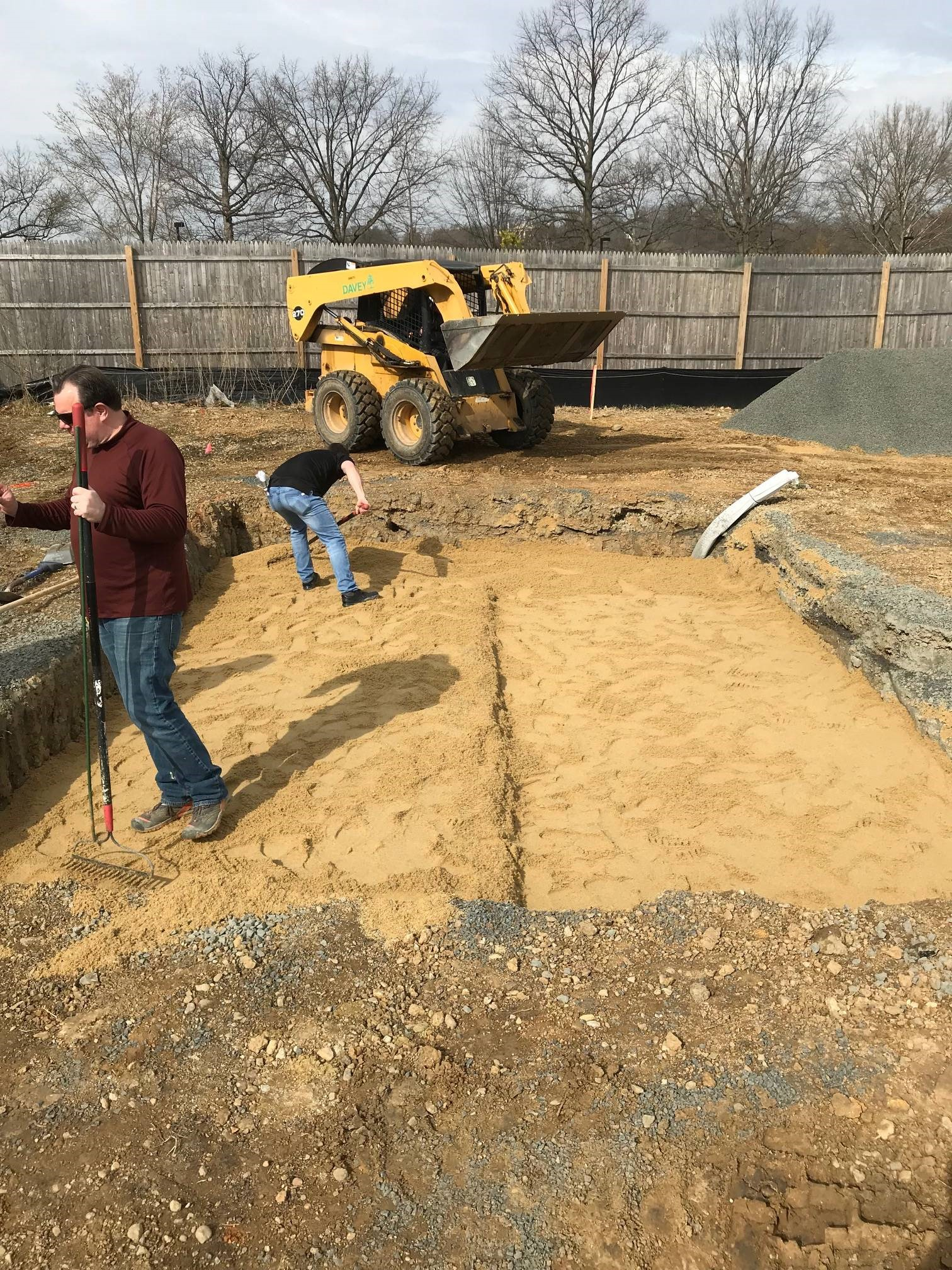 ANC horticulture staff installing a sand layer on an in-ground crypt