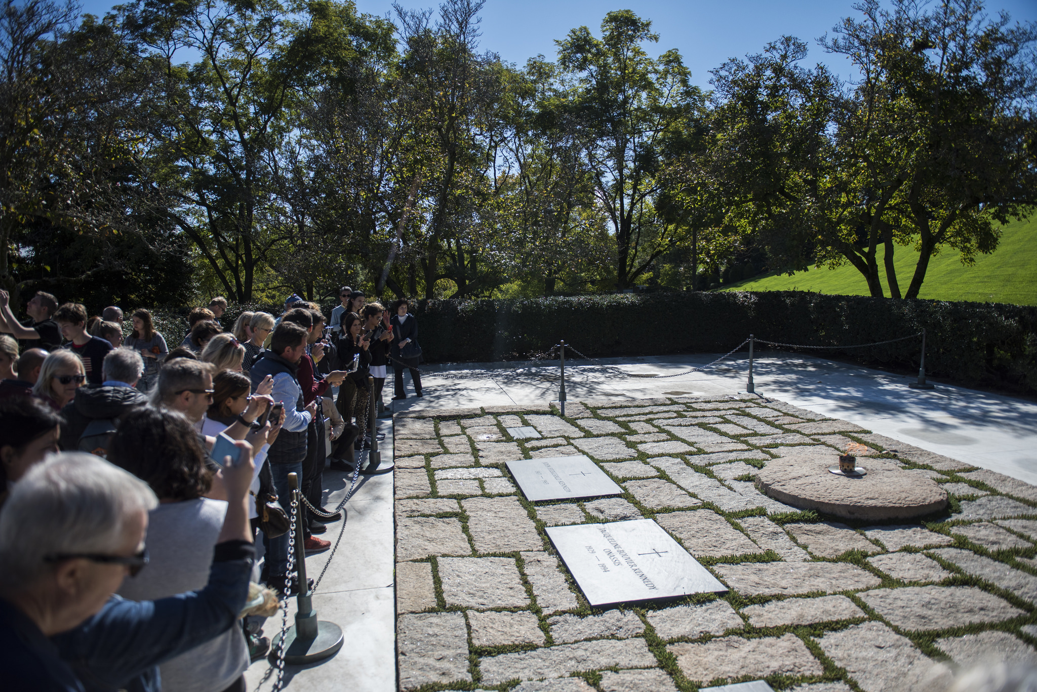 Visitors take photographs of the eternal flame at the gravesite of John F. Kennedy