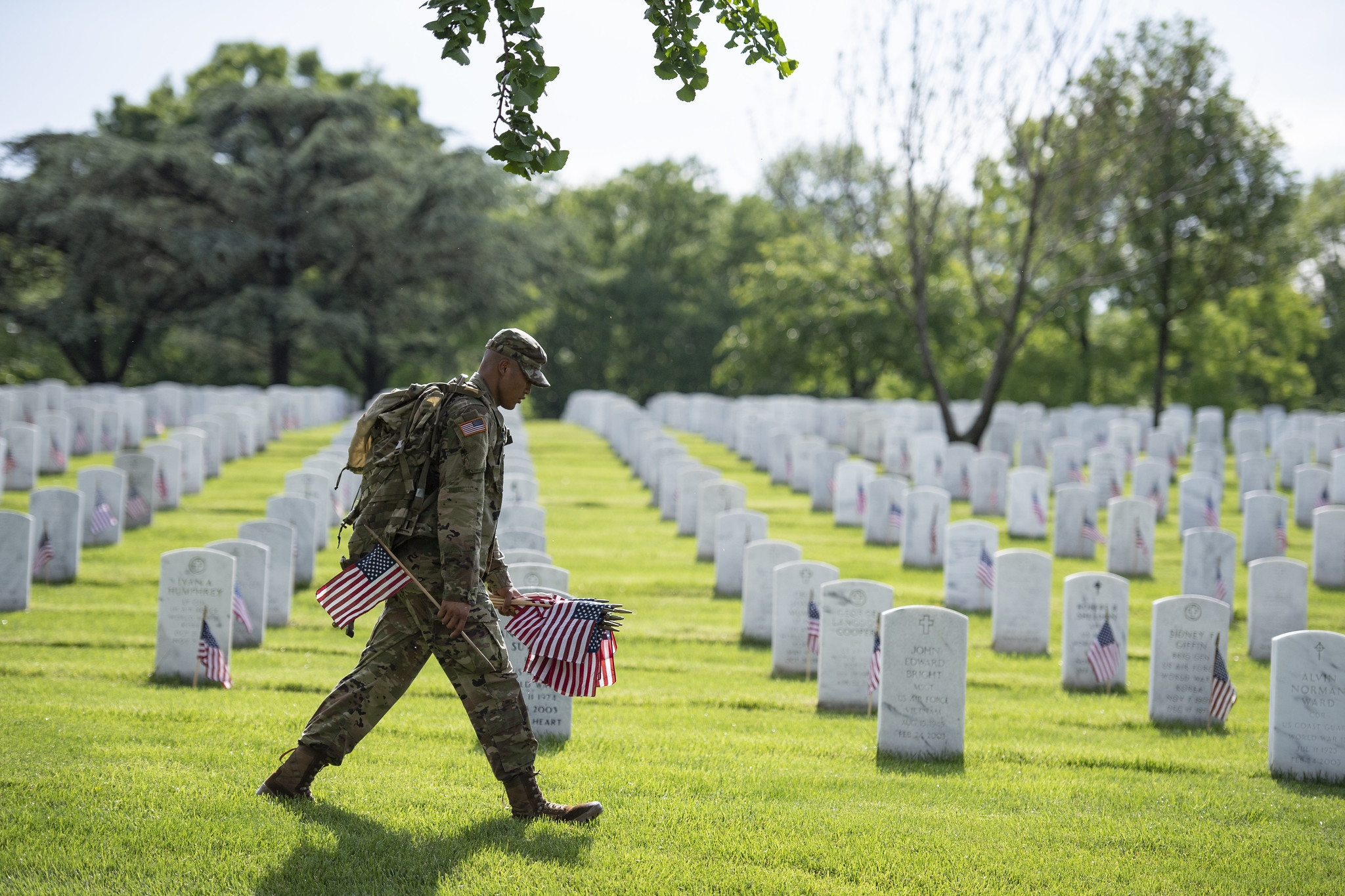 A soldier from the U.S. Army's 3rd Infantry Regiment places flags in front of gravestones for Memorial Day