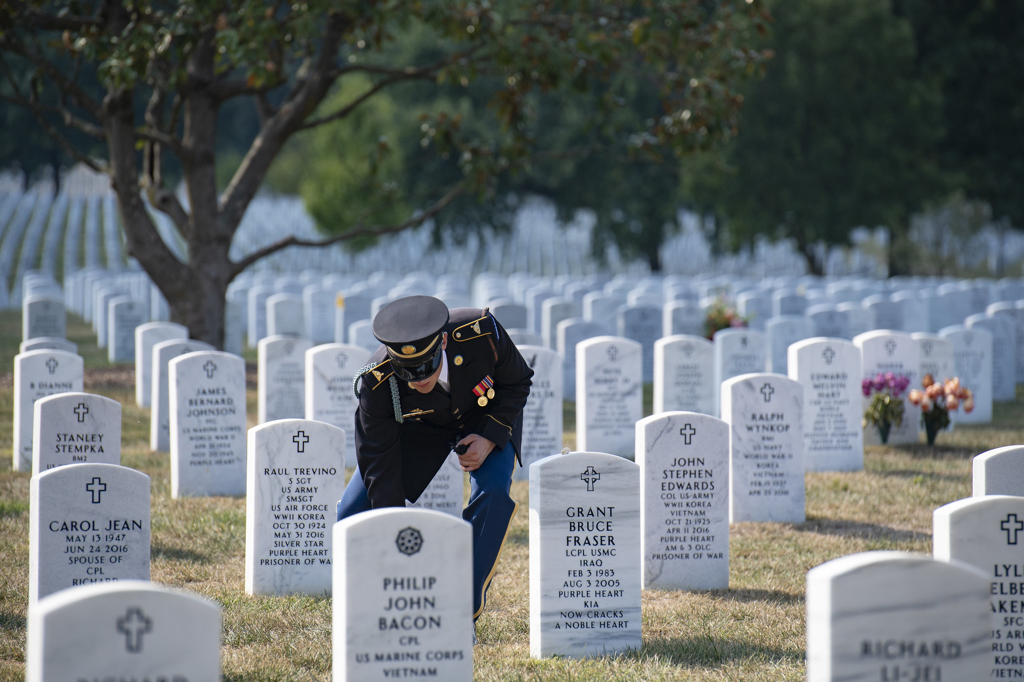 A uniformed soldier kneels before a gravestone at Arlington National Cemetery