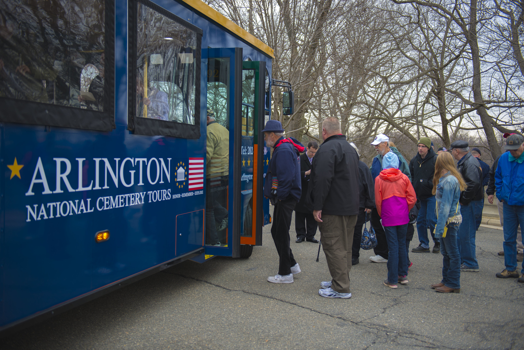 Visitors to Arlington National Cemetery board a tour bus